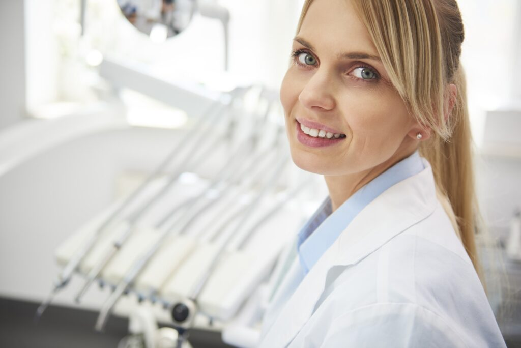 Image of female dentist posing for a photograph with dental equipment in the background